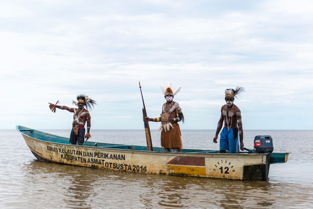 three decorated Asmat tribe men standing in a boat