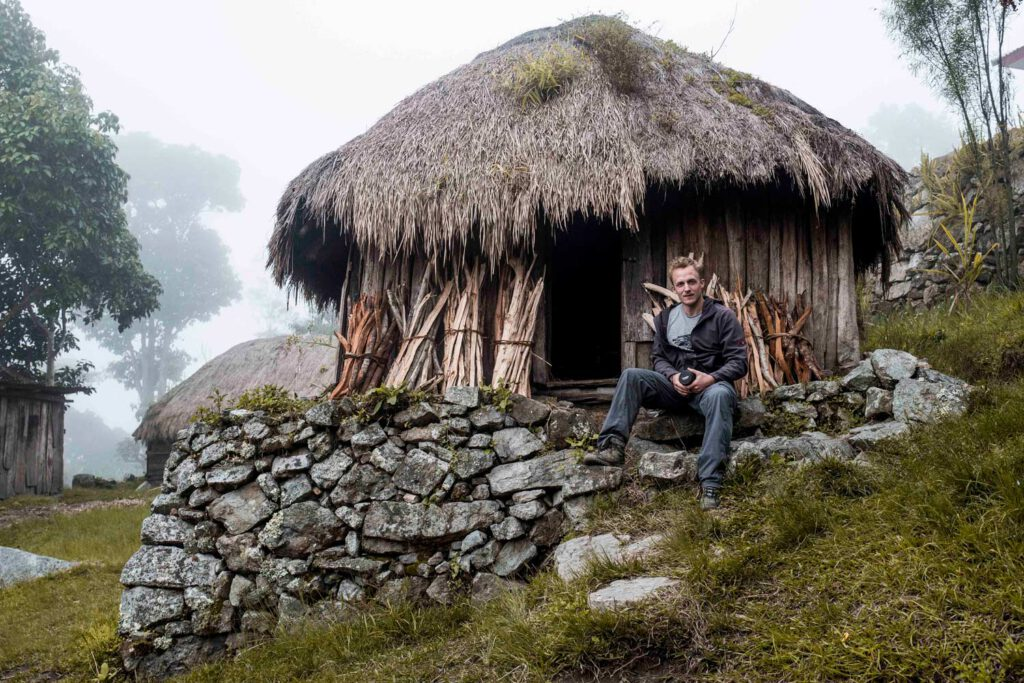 man sitting in front of a traditional house of the Baliem Valley in Papua