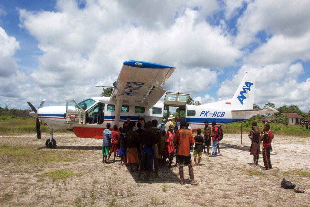 Gruppe von Personen, die vor einem Cessna Caravan Flugzeug stehen