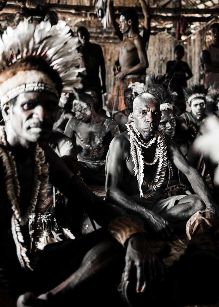 group of Asmat men with feather decoration sitting in a traditional house