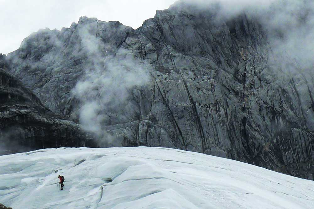 man walking on glacier with carstensz pyramid in background