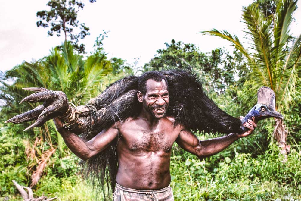 man carries cassowary on shoulder
