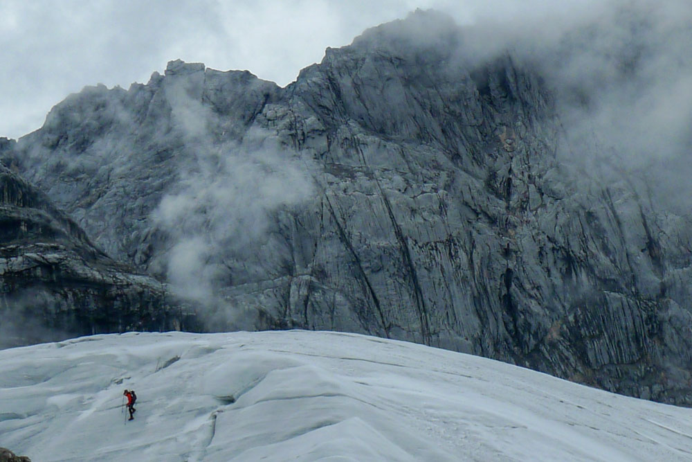 ice glacier with mountain climber and clouds