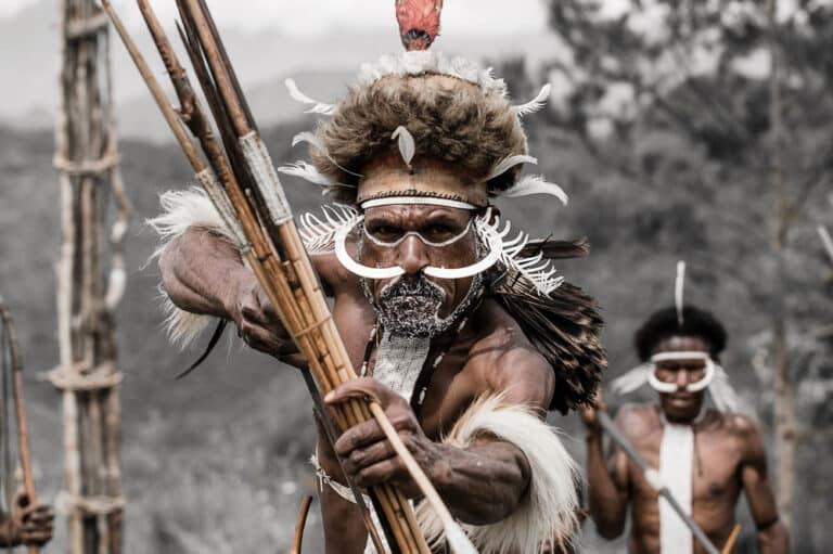 Dani warrior presenting bow and arrow