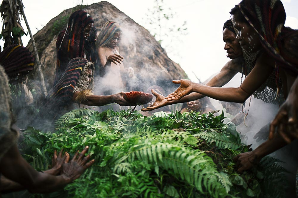 women hands reaching over cooking pit