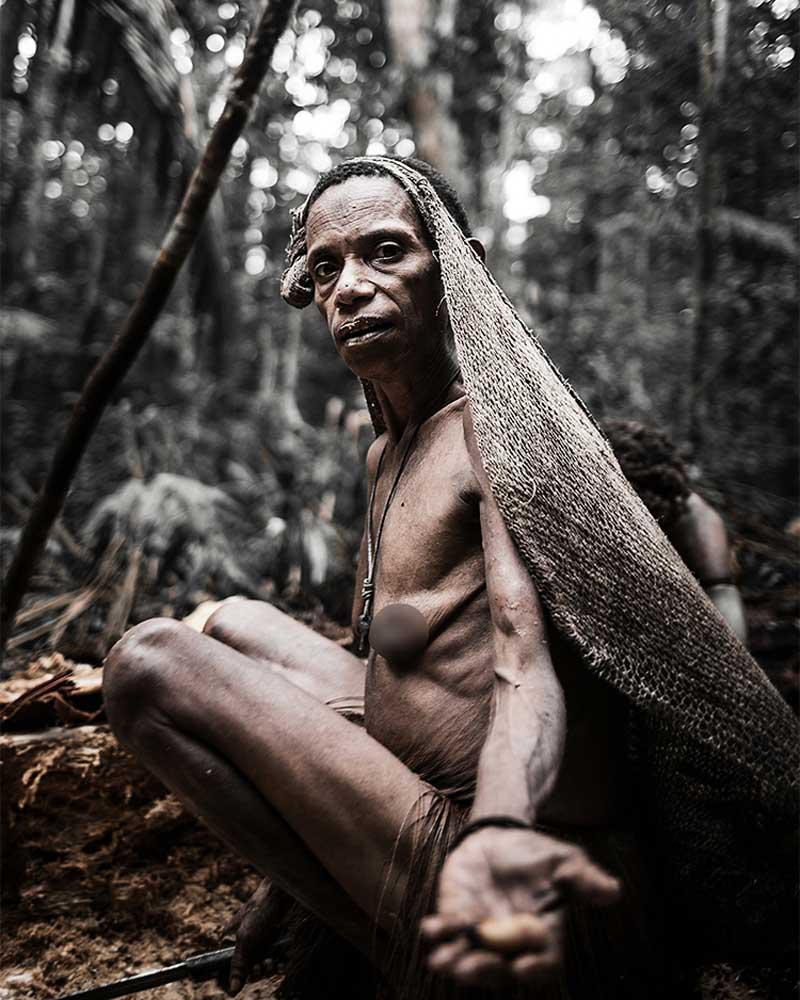 Korowai woman squatting presenting sago grub